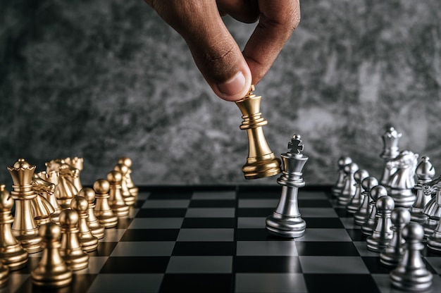 Mano dell'uomo che gioca scacchi per pianificazione aziendale e confronto della metafora, fuoco selettivo
