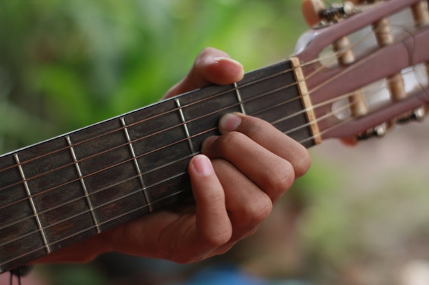 The hand of a man playing guitar and music
