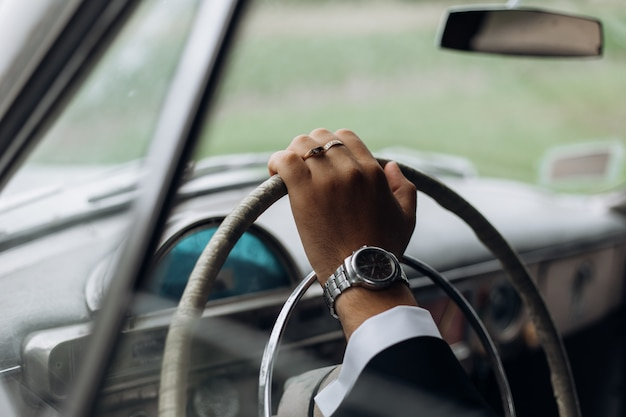 Hand of a man on the steering wheel of an old fashioned car, man's watch