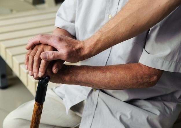Hand of man touching hands elderly man