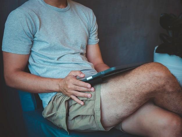 Рука человека с помощью цифрового планшета. молодой человек, мужчина в повседневной серой рубашке и шортах, сидит дома и взаимодействует с технологиями. бизнесмен релаксации, работающий онлайн в любом месте концепции.