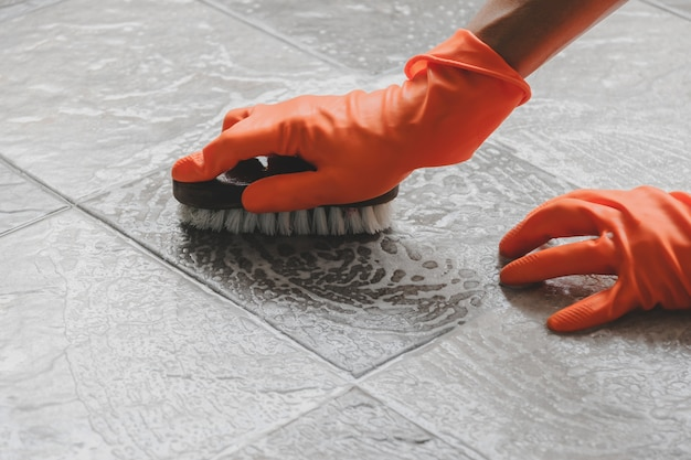 Hand of man wearing orange rubber gloves is use a hose to clean the tile floor.
