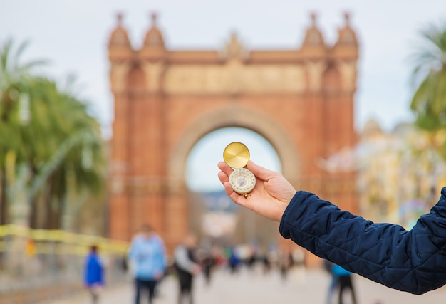 Hand of a man with a compass barcelona arc de triomphe. selective focus.