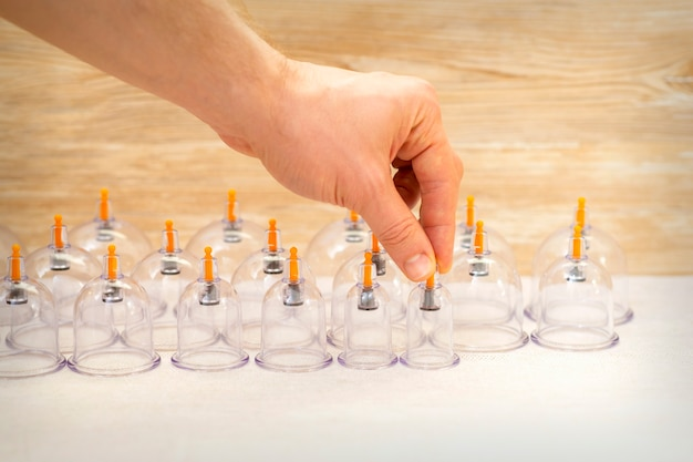 Hand of massage therapist taking vacuum cups from the table before cupping procedures
