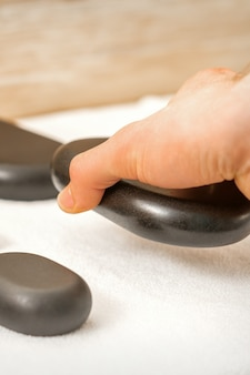 Hand of masseur lays out massage stones on the table in spa salon