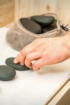 Hand of masseur takes hot black massage stones from table in spa