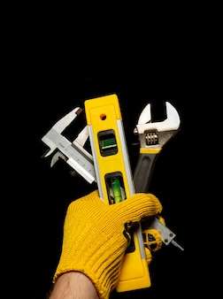 The hand of the master holds a set of tools