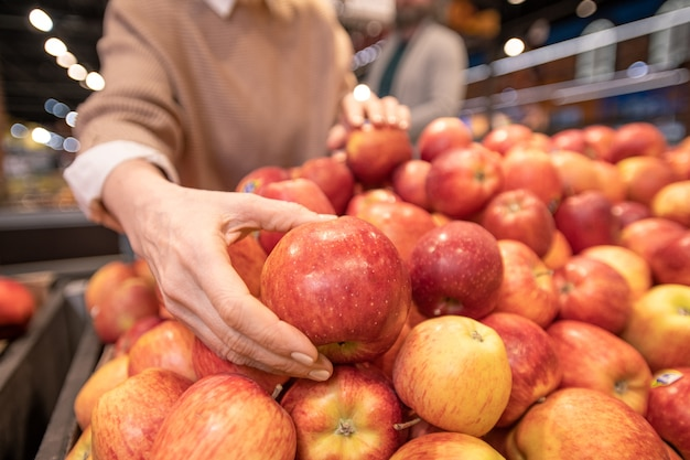 Hand of mature female customer choosing fresh red apples on fruit display while buying food products with her husband in supermarket