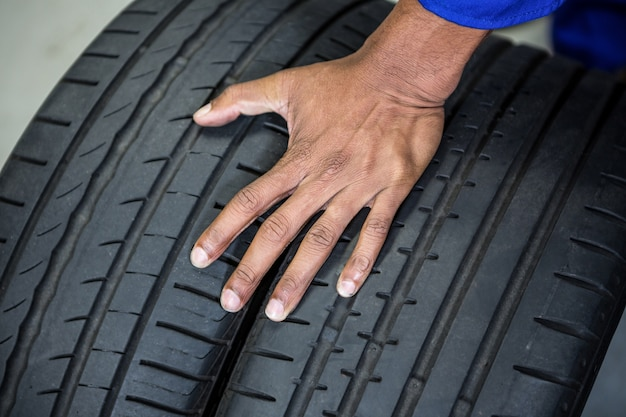Hand of mechanic holding tyres