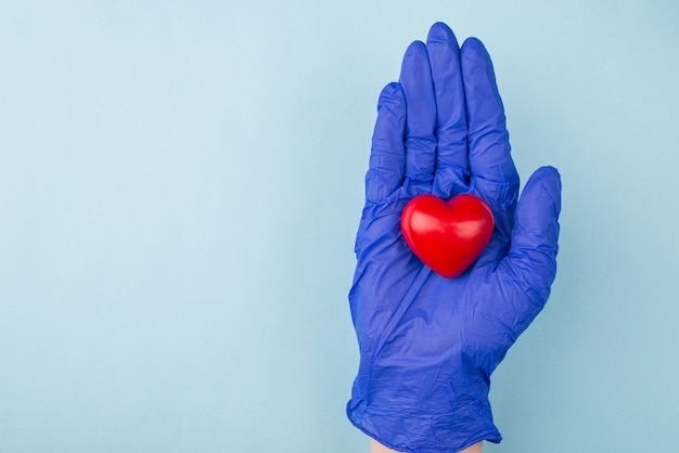 Hand in medical glove holding small red heart