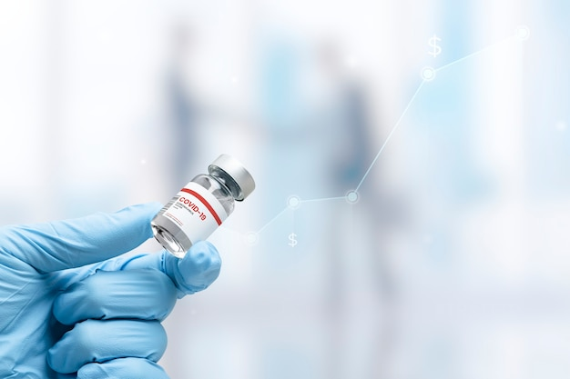 Hand in medical glove holding a vaccine vial