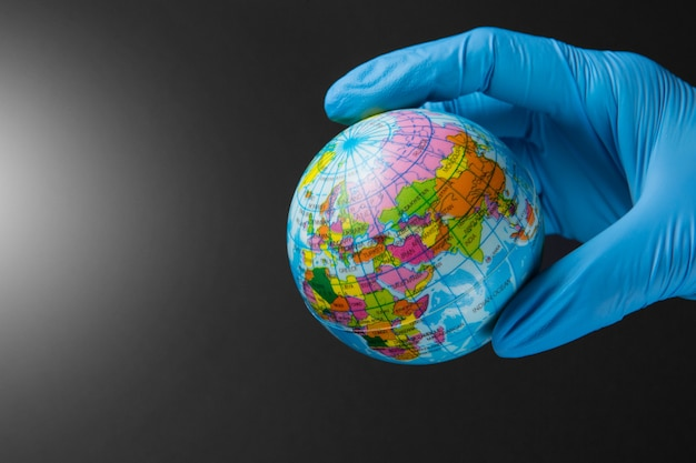 Hand in a medical glove holds a mockup of the planet earth, concept of the global epidemic of coronavirus