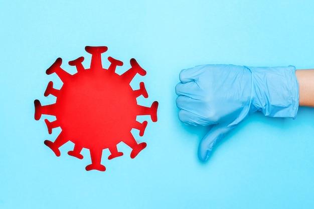 Hand in medical glove showing dislike gesture and red coronavirus