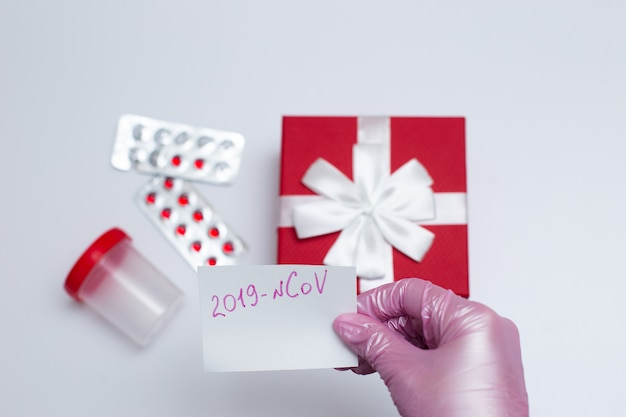 A hand in medical gloves holds a white card with the name of the coronavirus Premium Photo