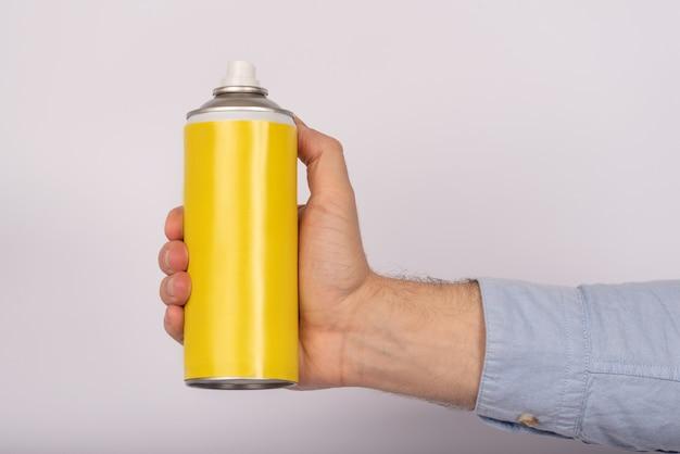 黄色のスプレー式塗料を持った男性の手。白い背景に碑文なし。モックアップ