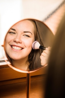 Hand mirror with reflection of happy woman applying blusher on her face