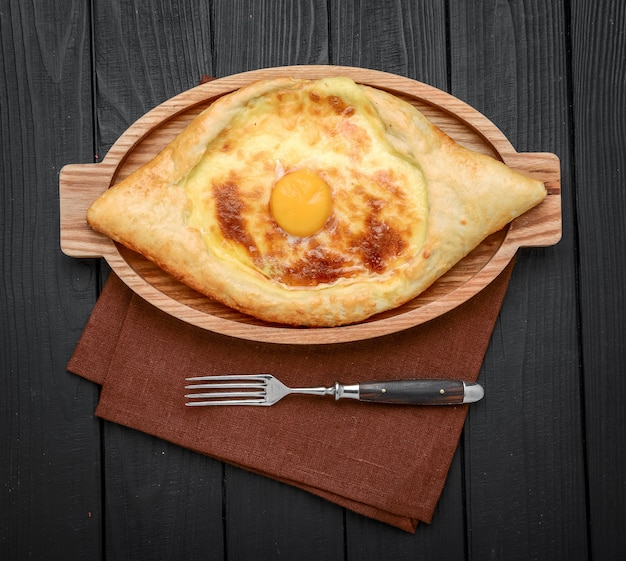 Hand mixing ingredients of adjarian khachapuri with fork in restaurant. open bread pie with cheese and egg yolk. yummy georgian cuisine.