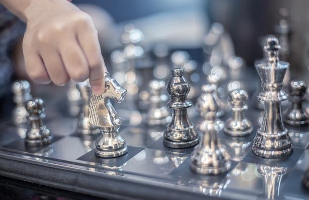 Hand move silver hourse model on board strategic game