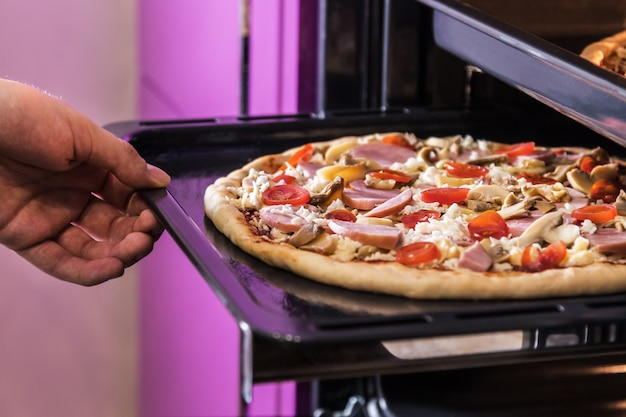 Hand moves the tray of pizza with mushrooms, ham and mozzarella