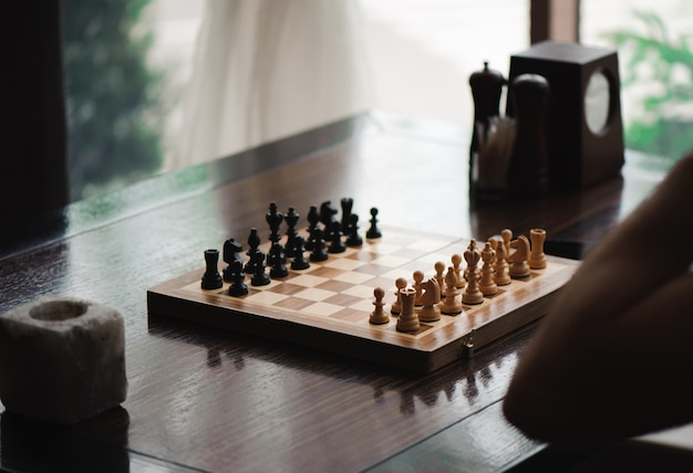 Hand moving chess figure in competition success play.