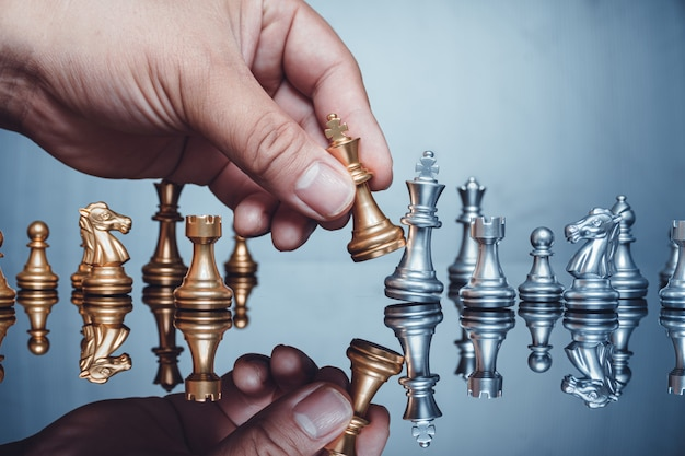 Hand moving golden king piece chess figure in competition success play business strategy