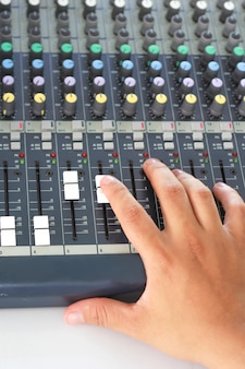 Hand moving the level on audio mixer.