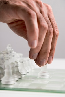 Hand moving transparent chess pieces