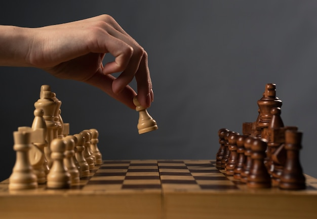 Hand moving white pawn and making first step