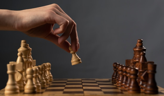 Hand moving white pawn and making first step.