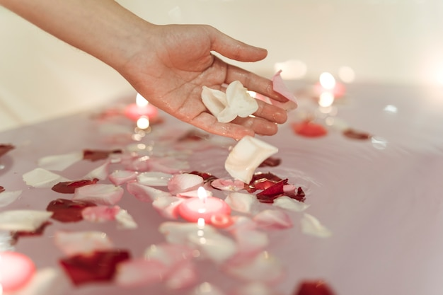 Hand near flower petals on water near burning candles