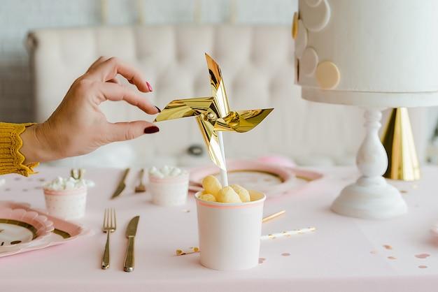 女の子の誕生日の装飾的なパーティーテーブルの上の紙コップで黄金の風車の近くに手