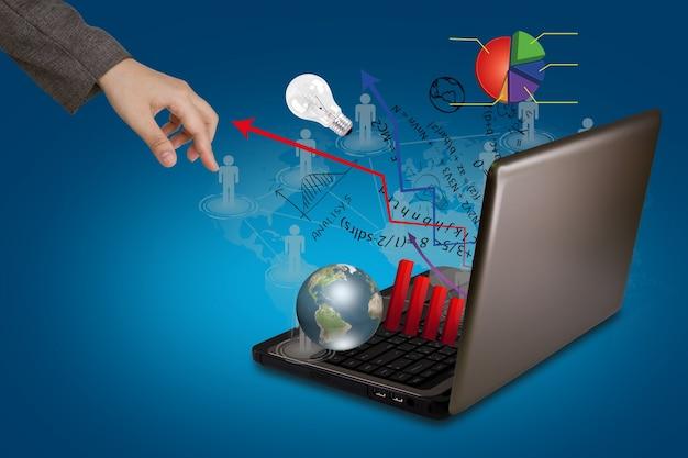 A mano nei pressi di un computer portatile che espelle la grafica e frecce