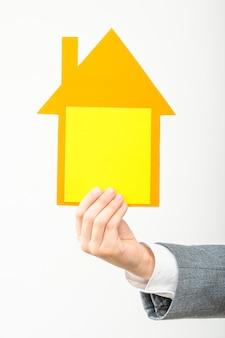 Рука мальчика с желто-оранжевым картонным домиком в руке