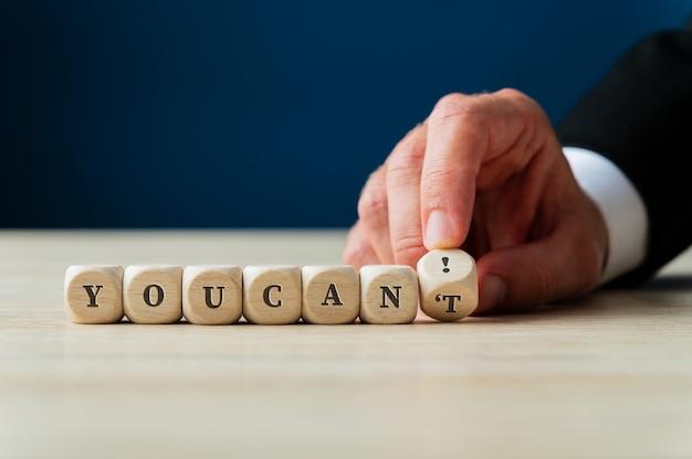 Рука бизнесмена меняет знак «ты не можешь подписать на деревянных кубиках» на «ты можешь!» перевернув последний кубик.