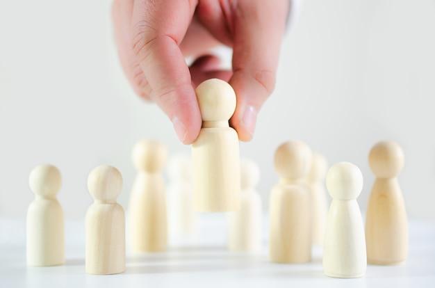 Рука бизнесмена выбирая деревянную диаграмму в схематическом изображении поиска, найма, тактик дела и стратегии, управления.