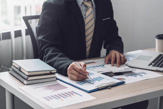 사무실에서 통계를 계산하기 위해 그래프 계산기를 가리키는 펜을 들고 있는 사업가의 손.