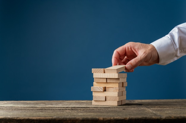 Рука бизнесмена, делая стопку деревянных колышков