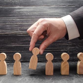 ビジネスマンの手は男の木製の姿を取ります検索採用と解雇労働者の昇進の概念ビジネスの戦術と戦略