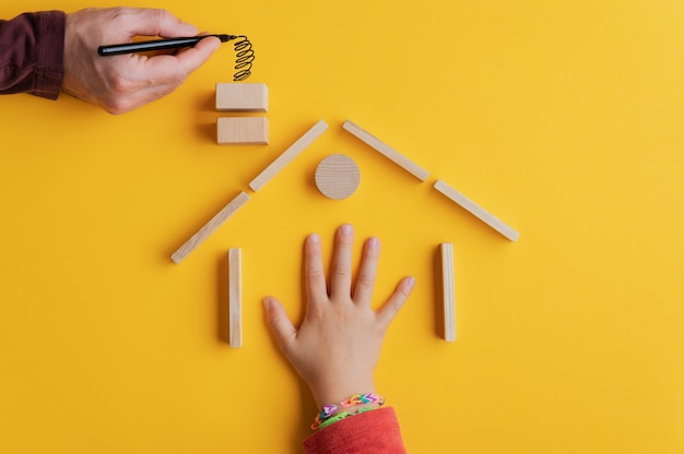 Рука ребенка в доме, построенном из деревянных колышков и блоков, с мужской рукой, тянущей дым из трубы в концептуальном образе домовладения. на желтом фоне.