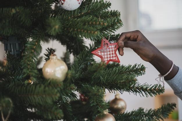 それを飾る過程でクリスマスツリーに赤いホリデースターをぶら下げている色の女の子の手。
