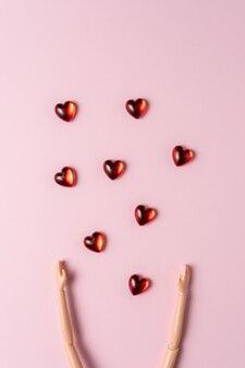 Рука куклы с маленькими сердечками на розовой поверхности.