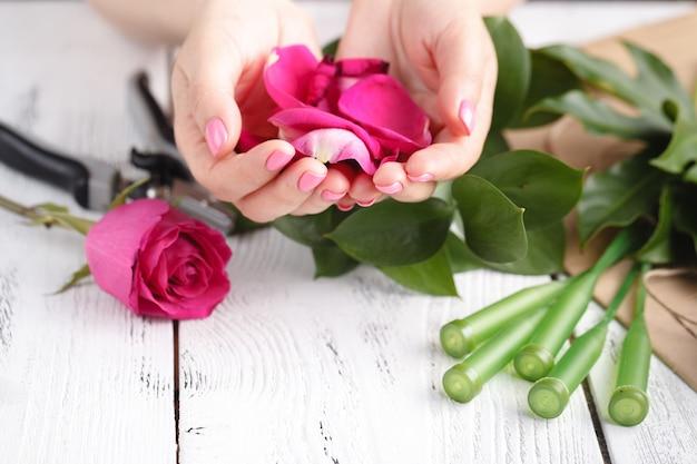 結婚式のためのバラの花びらでいっぱいの花屋の女性の手
