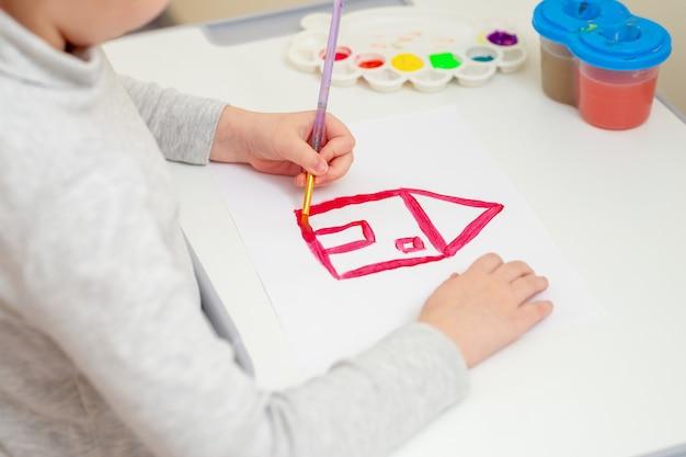 Рука девушки рисуя красный дом.