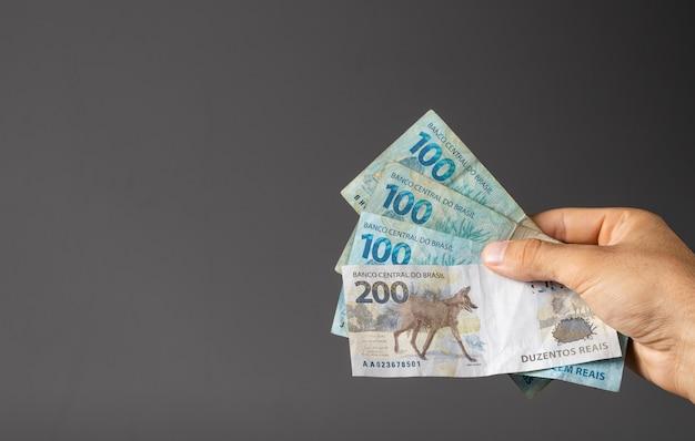 ブラジルの紙幣を持っている男の手