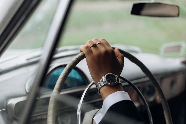 昔ながらの車、男の時計のステアリングホイール上の男の手