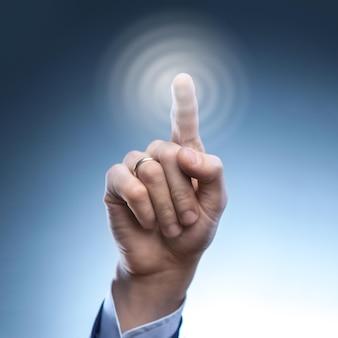 仮想表面でハイテクタイプのモダンなボタンを押す男の手