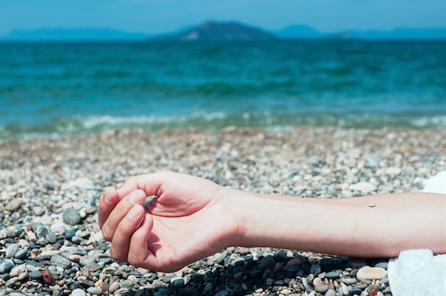 バックグラウンドで青緑色の海の水、ビーチでリラックスした男の手