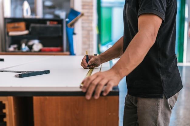 ワークショップで鉛筆を使用して表面の測定点をマークする男の手