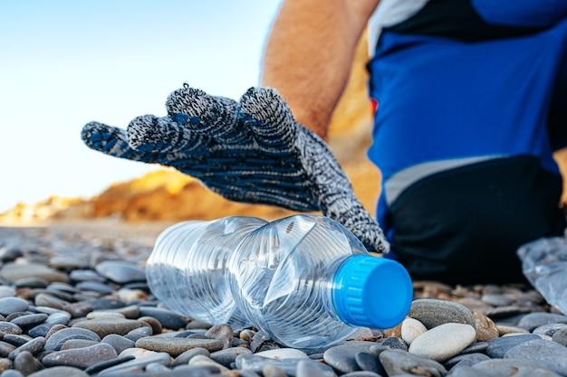 プラスチックごみをゴミ袋につかんでビーチを掃除するボランティアの男性の手がクローズアップ