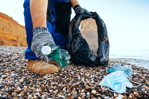 Рука человека-волонтера хватает пластиковый мусор в мешок для мусора, убирая пляж крупным планом